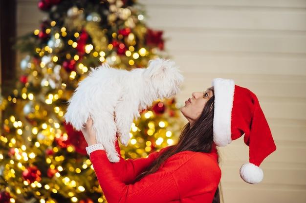 Dziewczyna Trzyma Małego Psa Na Rękach Na Choince Darmowe Zdjęcia