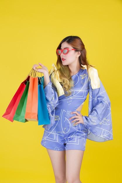 Dziewczyna trzyma modną torbę na zakupy i trzyma kartę inteligentną na żółtym tle. Darmowe Zdjęcia