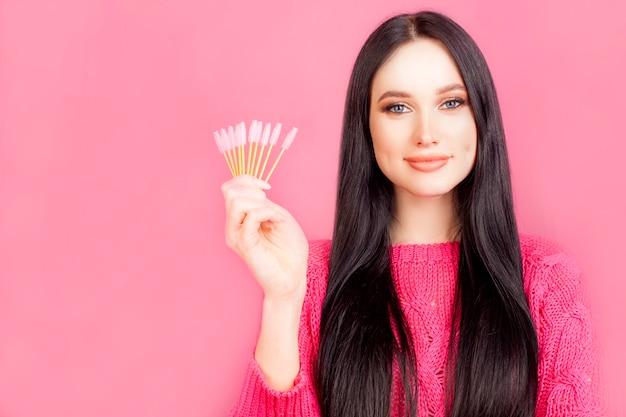 Dziewczyna Trzyma Pędzle Do Rzęs, Model Z Makijażem, Na Różowym Tle. Mistrz Makijażu, Tuszu Do Rzęs Lub Przedłużania Rzęs. Premium Zdjęcia