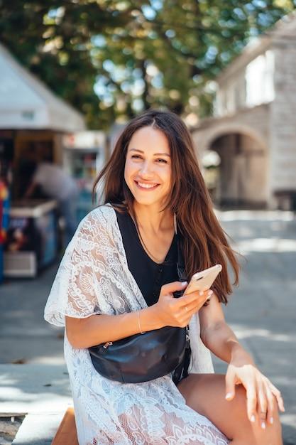 Dziewczyna trzyma telefon i pozuje w aparacie. internet wiadomość. Darmowe Zdjęcia