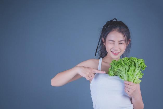 Dziewczyna trzyma warzywa na szarym tle. Darmowe Zdjęcia