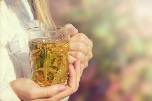 Dziewczyna trzyma z bliska ciepłe, rozgrzewające herbaty ziołowe Premium Zdjęcia