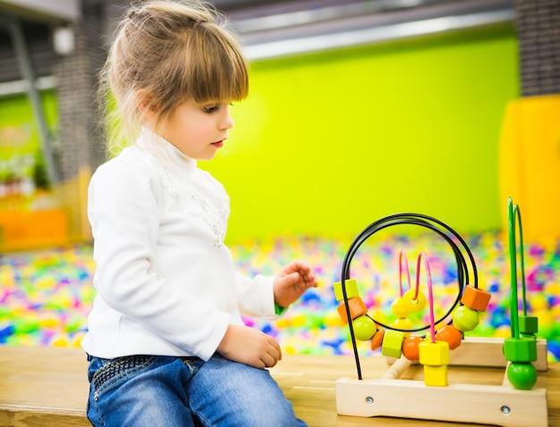 Dziewczyna Ubrana W Dżinsy I Biały Sweter Bawi Się Rozwijającą Się Drewnianą Zabawką W Pokoju Zabaw Premium Zdjęcia