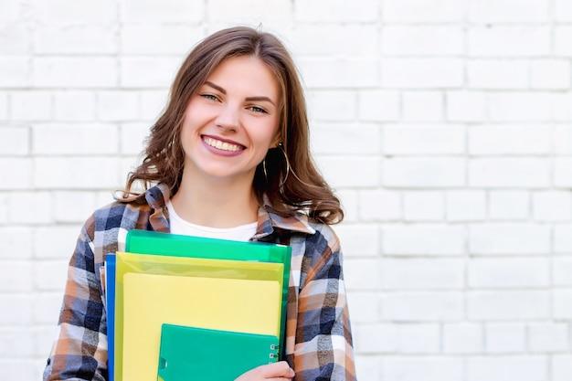 Dziewczyna uczeń trzyma w rękach falcówki i notatnika i ono uśmiecha się na tle biały ściana z cegieł Premium Zdjęcia