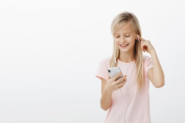 Dziewczyna Ukradła Mamie Telefon, Aby Obejrzeć Nową Serię Ulubionej Kreskówki. Zadowolony Figlarny Dziecko Płci żeńskiej O Blond Włosach, Słuchanie Muzyki W Słuchawkach I Uśmiechanie Się Do Ekranu Smartfona Podczas Grania W Gry Darmowe Zdjęcia