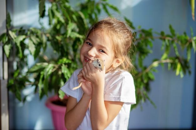 Dziewczyna W Białej Koszulce Trzyma Mongolską Myszoskoczkę Na Dłoni. Dziecko I Nasi Mniejsi Bracia Premium Zdjęcia