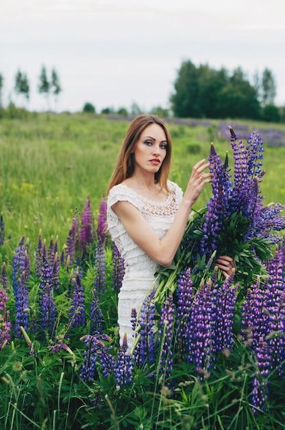 Dziewczyna w białej sukni stoi wśród łubinów Premium Zdjęcia