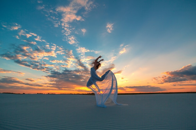 Dziewczyna w białej sukni w locie tańczy i pozuje na piaszczystej pustyni o zachodzie słońca Premium Zdjęcia