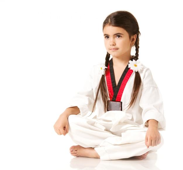 Dziewczyna W Białym Kimono Siedzi W Pozie Jogi Premium Zdjęcia