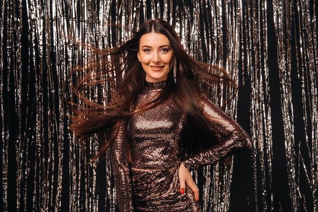 Dziewczyna W Błyszczącej Sukience Na Srebrnym Tle Noworocznego Deszczu Z Rozwijającymi Się Włosami. Premium Zdjęcia