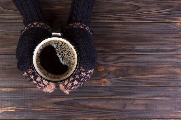 Dziewczyna w ciepłe ubrania i rękawiczki trzyma w rękach biały kubek. Premium Zdjęcia