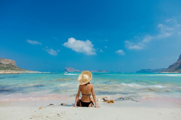 Dziewczyna W Czarnym Bikini I Kapeluszu Na Plaży Balos Premium Zdjęcia