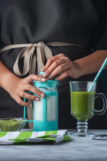 Dziewczyna W Czarnym Fartuchu Przygotowuje Latte Z Zielonej Herbaty Matcha. Premium Zdjęcia
