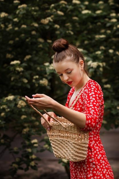 Dziewczyna W Czerwonej Sukience Ze Słomianą Torbą W Naturze W Lecie Premium Zdjęcia