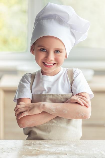 Dziewczyna w fartucha i szefa kuchni kapeluszu jest przyglądającym kamerą i ono uśmiecha się. Premium Zdjęcia