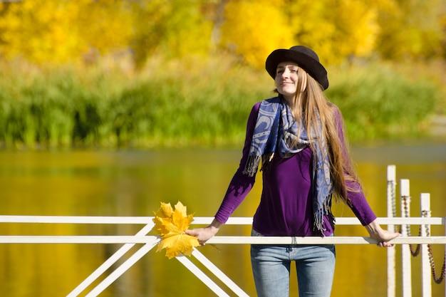 Dziewczyna w kapeluszowej pozyci na doku Premium Zdjęcia