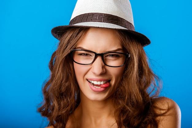 Dziewczyna w kapeluszu gryzie język Premium Zdjęcia