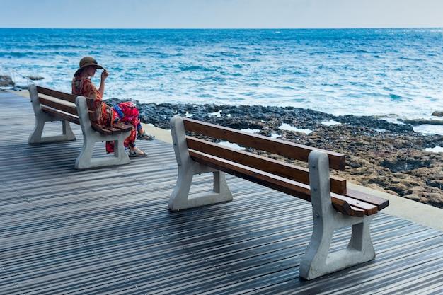 Dziewczyna W Kapeluszu Na ławkach Nad Morzem Premium Zdjęcia