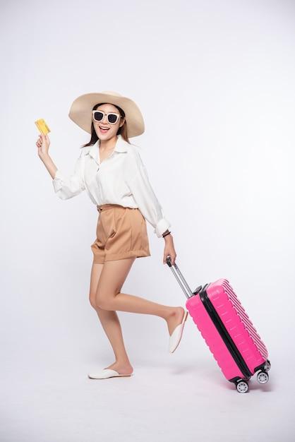Dziewczyna W Kapeluszu, Trzymając Walizkę I Kartę Kredytową Do Podróży Darmowe Zdjęcia