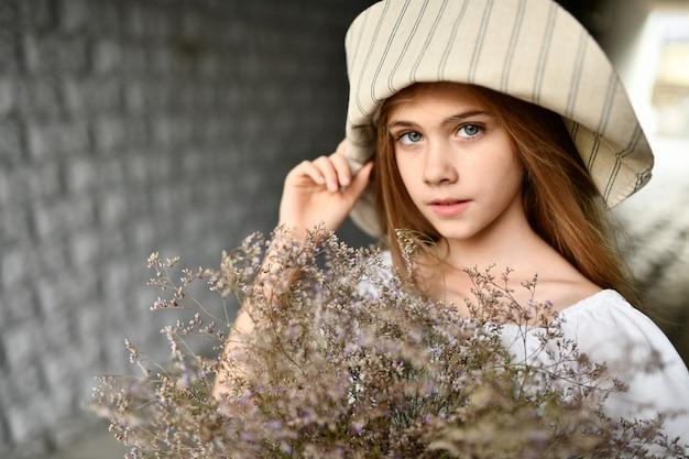 Dziewczyna W Kapeluszu Z Kwiatami. Premium Zdjęcia
