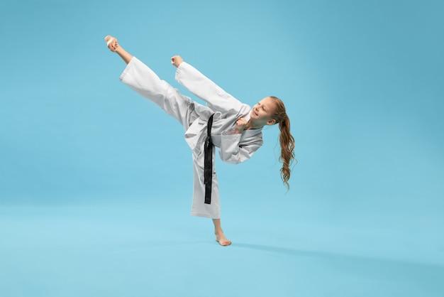 Dziewczyna W Kimono ćwiczy Kopnięcie Stopę Do Przodu. Darmowe Zdjęcia