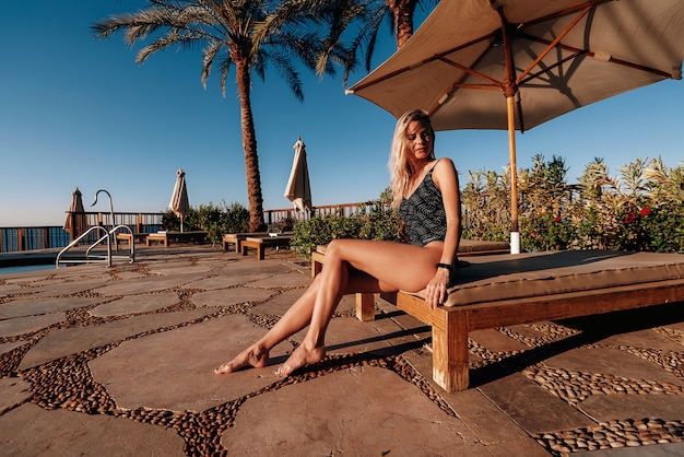 Dziewczyna W Kostiumie Kąpielowym Na Plaży Przy Basenie W Gorącym Słońcu Relaksuje Się Na Wakacjach Premium Zdjęcia