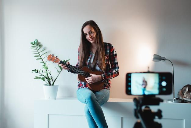 Dziewczyna W Koszuli I Dżinsach Pisze Na Telefonie Vloga O Grze Na Ukulele. Premium Zdjęcia