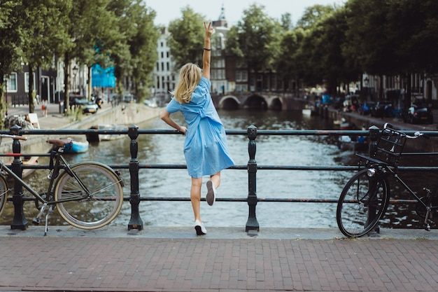 Dziewczyna w niebieskiej sukience na moście w amsterdamie Darmowe Zdjęcia