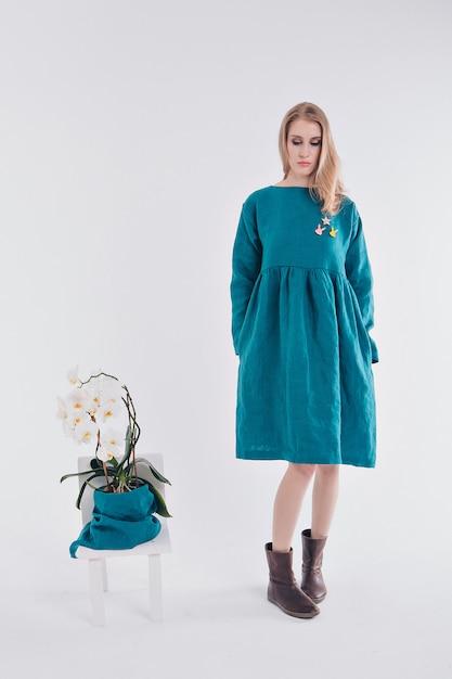 Dziewczyna w niebieskiej sukience obok kwiatu w doniczce Premium Zdjęcia