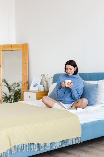 Dziewczyna W Niebieskim Swetrze We Wnętrzu W Stylu Hygge Z Filiżanką Gorącej Herbaty W Dłoniach Siedzi Na łóżku Premium Zdjęcia