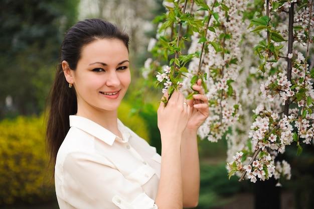Dziewczyna w parku wiosną w pobliżu kwitnących drzew. Premium Zdjęcia