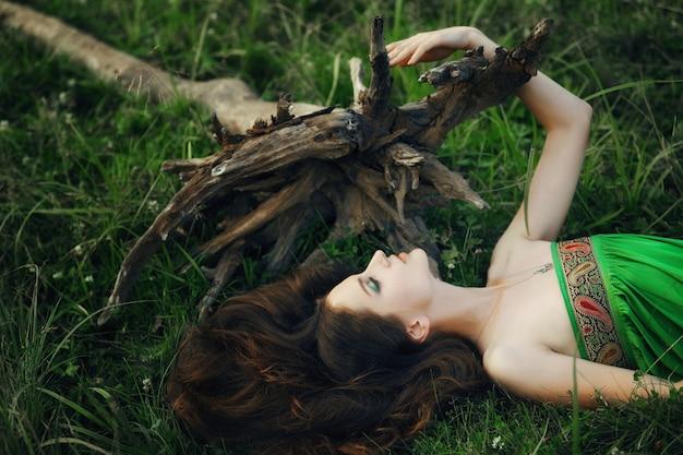 Dziewczyna W Pięknej Zielonej Sukience Leży Na Trawie W Pobliżu Korzeni Drzewa I Marzy. Kobieta Z Jasny Makijaż W Przyrodzie, Naturalne Kosmetyki Premium Zdjęcia
