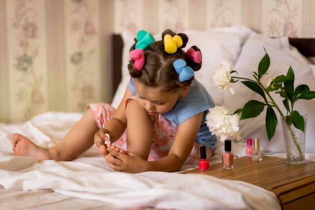 Dziewczyna W Piżamie I Papilotach Maluje Paznokcie Premium Zdjęcia