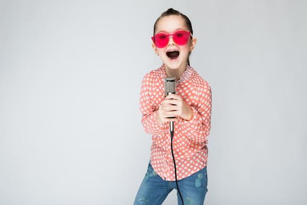 Dziewczyna w pomarańczowej koszula, szkłach i niebieskich dżinsach na szarość Premium Zdjęcia
