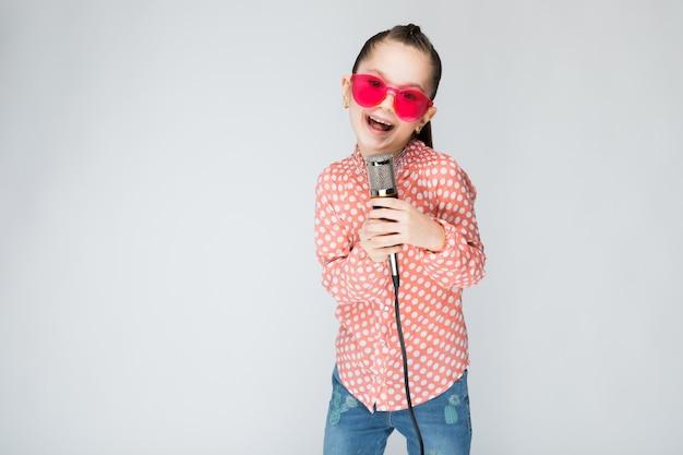 Dziewczyna w pomarańczowej koszula, szkłach i niebieskich dżinsach Premium Zdjęcia