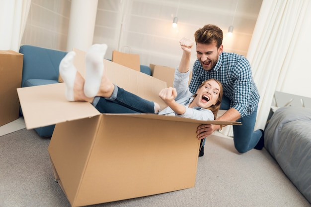 Dziewczyna w pudełku i facet toczy ją po mieszkaniu Premium Zdjęcia