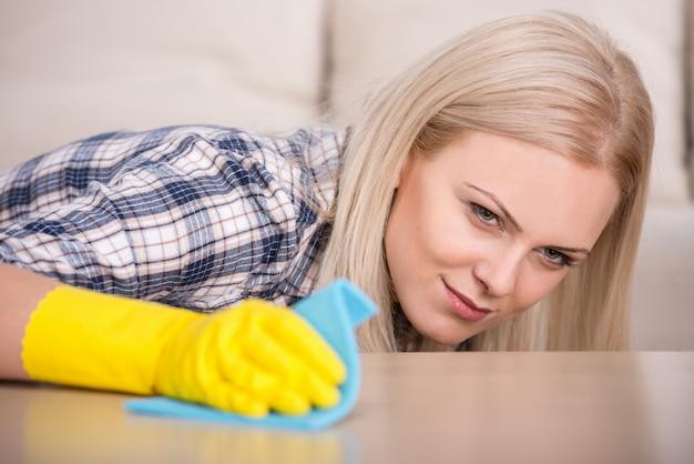 Dziewczyna w rękawiczkach czyści stół szmatką. Premium Zdjęcia