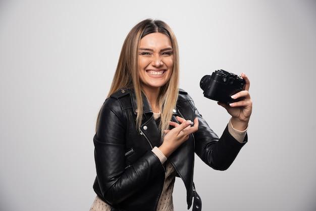 Dziewczyna W Skórzanej Kurtce Sprawdzanie Jej Historii Zdjęć W Aparacie Darmowe Zdjęcia