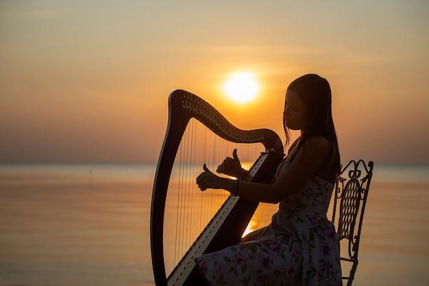 Dziewczyna W Sukience Z Kwiatami Bawi Się Na Harfie Celtyckiej Nad Morzem O Zachodzie Słońca Premium Zdjęcia