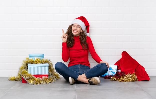 Dziewczyna w święta bożego narodzenia, siedząc na podłodze, wskazując palcem wskazującym, świetny pomysł Premium Zdjęcia