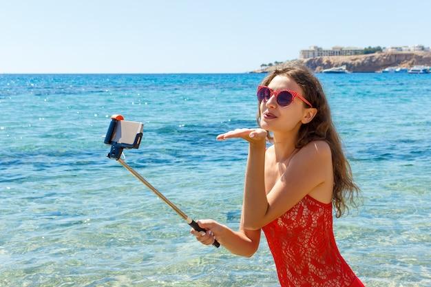 Dziewczyna W Swimsuit Z Mądrze Telefonem Na Plaży. Dziewczyna Biorąc Zabawy Selfie Na Plaży Premium Zdjęcia