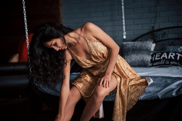 Dziewczyna W Złotej Sukni Siedzi Przy Białym łóżku Na łańcuchach W Luksusowych Apartamentach Premium Zdjęcia