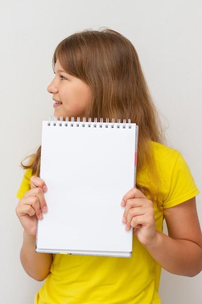 Dziewczyna W żółtej Koszulce Z Pustym Notatnikiem W Rękach. Dziewczynka Dziecko Trzyma Pustą Książkę. Wolne Miejsce Na Tekst. Premium Zdjęcia