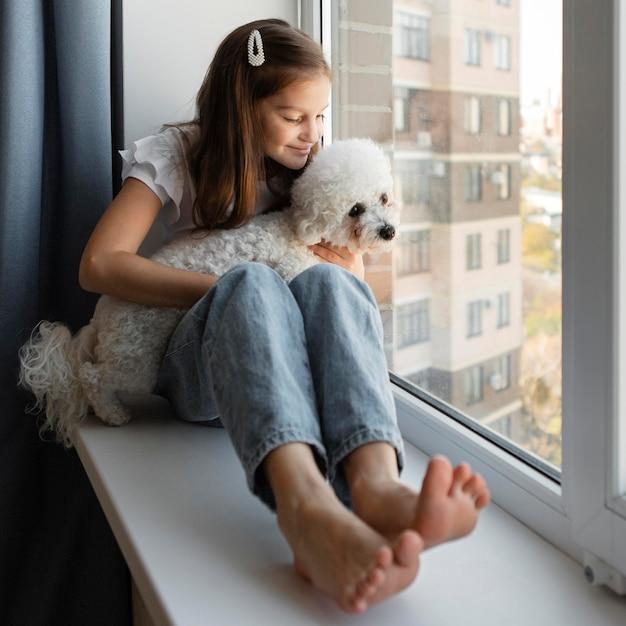 Dziewczyna Wygląda Przez Okno Z Psem W Domu Darmowe Zdjęcia
