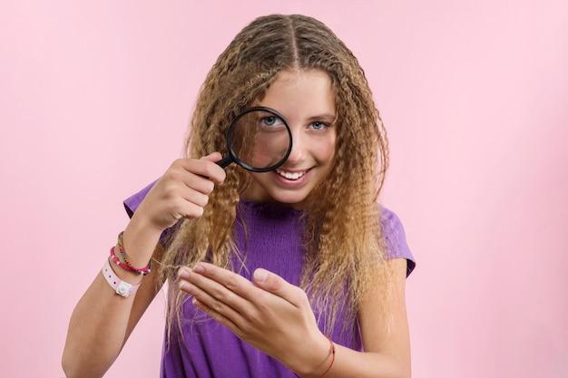 Dziewczyna z długimi blond włosami kręconymi patrząc przez szkło powiększające Premium Zdjęcia