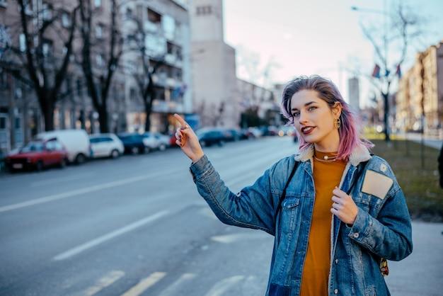 Dziewczyna z farbowanymi włosami przywołująca taksówkę. Premium Zdjęcia