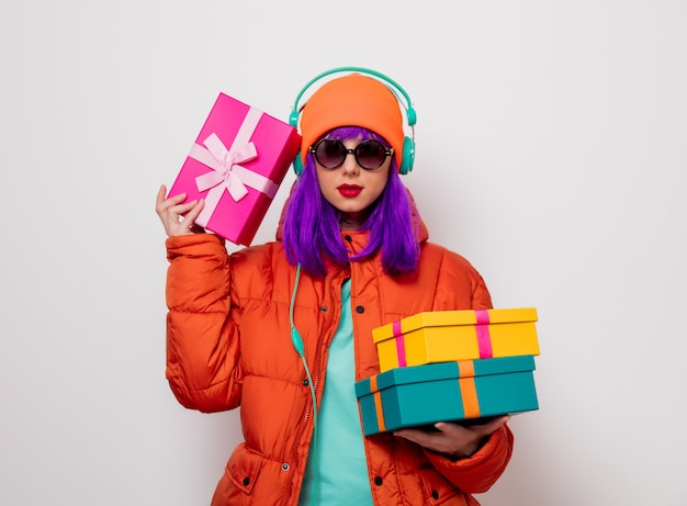 Dziewczyna z fioletowymi włosami ze słuchawkami i prezentami Premium Zdjęcia