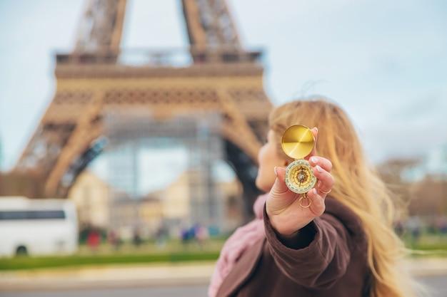 Dziewczyna Z Kompasem W Rękach W Pobliżu Wieży Eiffla W Paryżu. Selektywne Ustawianie Ostrości. Premium Zdjęcia