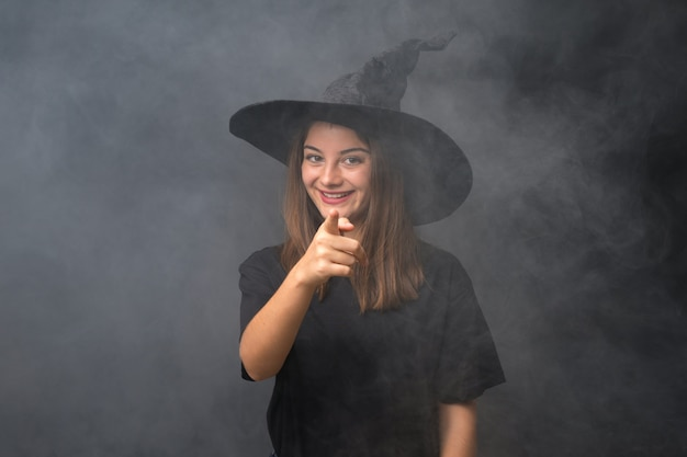 Dziewczyna z kostiumem wiedźmy na imprezy halloweenowe na pojedyncze ciemne punkty ściany palcem na ciebie Premium Zdjęcia