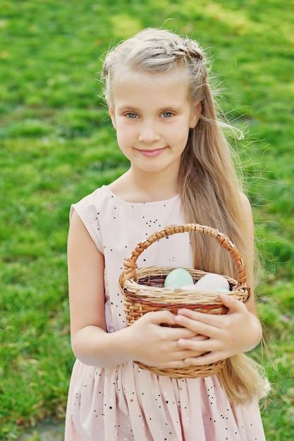 Dziewczyna z królikiem i jajkami na wielkanoc w parku na zielonej trawie Premium Zdjęcia
